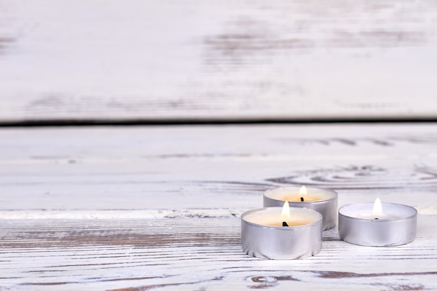 Three small burning candlelights on white wooden desk