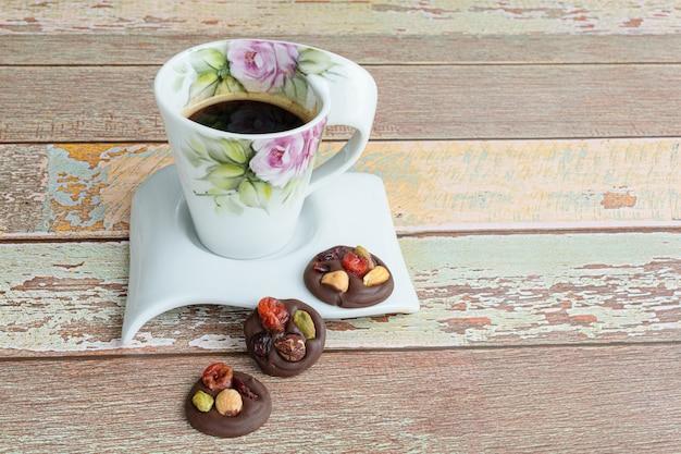 バラのデザインのコーヒーカップの横にある、ナッツ入りの3つの小さなチョコレートチップクッキー。