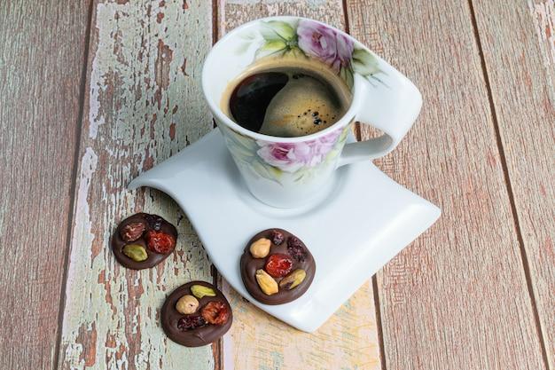 一杯のコーヒーの隣に、ナッツ入りの3つの小さなチョコレートチップクッキー。