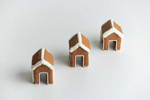 白い背景の上の3つの小さなジンジャーブレッドハウス。クリスマスの焼き菓子。冬の休日のパターン。
