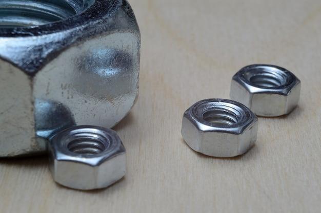 木製のテーブルのクローズアップに3つの小さなナットと1つの大きなナット。