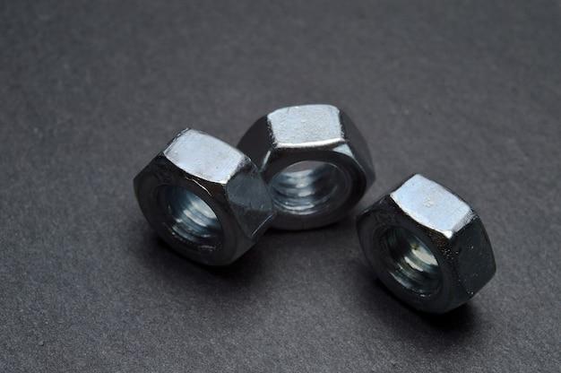 검은 질감 된 표면에 세 개의 작은 너트