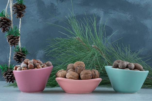 Three small plate full of nuts with christmas pinecones on marble background. high quality photo