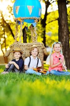 세 명의 어린 미취학 아동이 파란 풍선과 햇빛 바구니를 배경으로 잔디에 앉아 있습니다. 어린 시절, 모험, 휴가.
