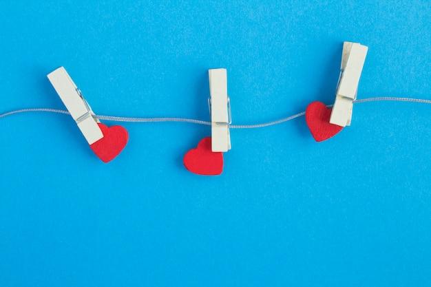 Три маленьких красных сердечек с деревянными прищепками на серой веревке на синем фоне. смотреть. копировать пространство
