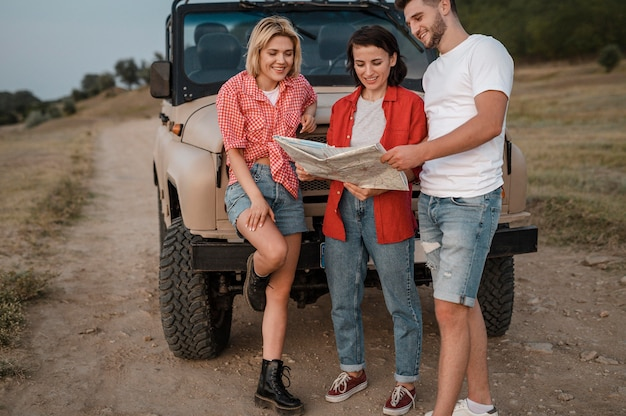 Three smiley friends checking map while traveling by car