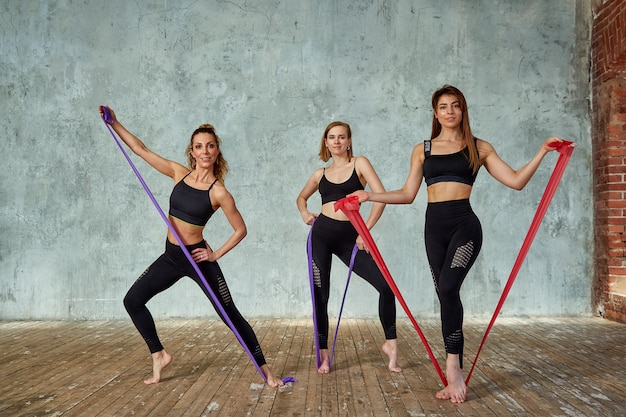 Three smiling beautiful, fitness girls posing in a fitness room. concept sport, teamwork.