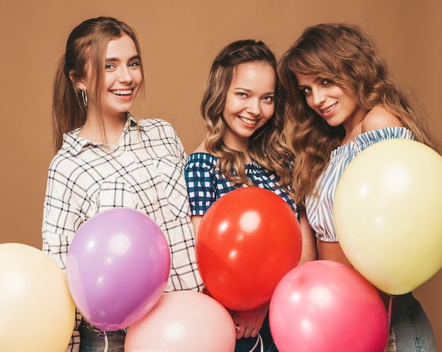 Three smiling beautiful women in checkered shirt summer clothes. girls posing. models with colorful balloons. having fun, ready for celebration birthday