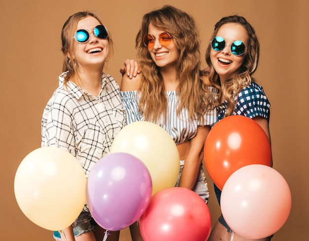 Three smiling beautiful women in checkered shirt summer clothes. girls posing. models with colorful balloons in sunglasses. having fun, ready for celebration birthday