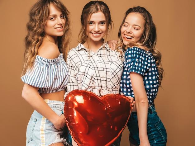 Tre belle donne sorridenti in abiti a scacchi estate camicia. ragazze in posa modelli con palloncino a forma di cuore. pronto per la festa di san valentino