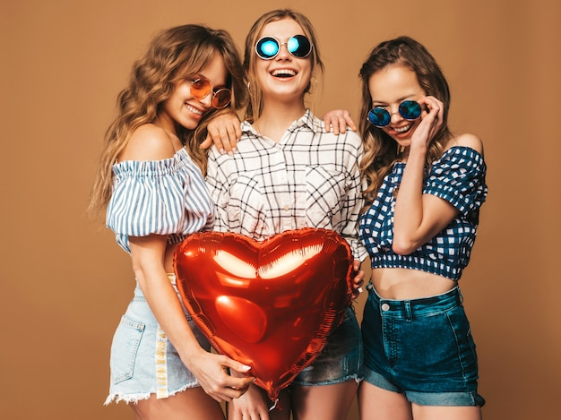 Three smiling beautiful women in checkered shirt summer clothes. girls posing. models with heart shape balloon in sunglasses. ready for celebration valentine's day