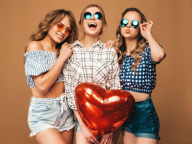 Tre belle donne sorridenti in abiti a scacchi estate camicia. ragazze in posa modelli con palloncino a forma di cuore in occhiali da sole. pronto per la festa di san valentino