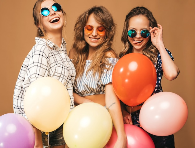Three smiling beautiful women in checkered shirt summer clothes and sunglasses. girls posing. models with colorful balloons. having fun, ready for celebration birthday