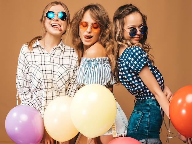Три улыбающиеся красивые женщины в клетчатой рубашке летней одежды. девушки в темных очках позируют. модели с разноцветными шарами. весело показывает язык