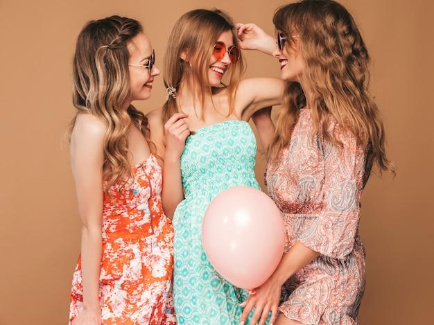 Три улыбающиеся красивые женщины в летних платьях. девочки позируют. модели с разноцветными шарами. веселимся, готовимся к празднованию дня рождения или праздничной вечеринки