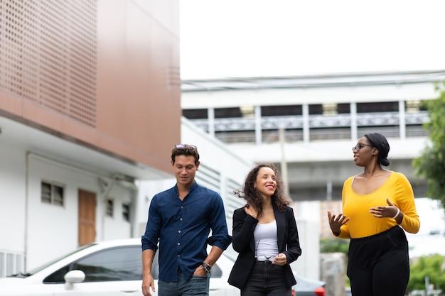 세 명의 웃고 있는 사업가들이 도시를 걷는 동안 회의에 대해 논의하고 있습니다.
