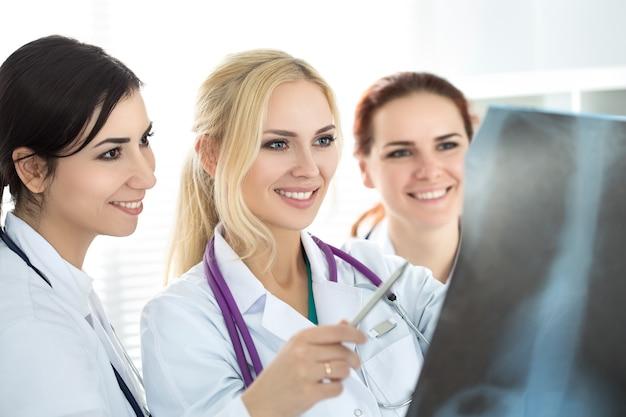 Три улыбается женщина-врач медицины, глядя на рентгеновский снимок. концепция здравоохранения и медицины.