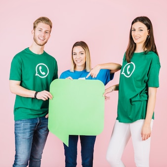 Three smiling friends holding empty green speech bubble