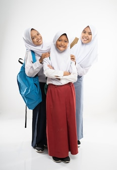 Three smiling girls wearing veils in school uniforms looking to the camera with school bags