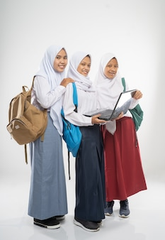 Three smiling girls wearing veils in school uniforms using a laptop together with school bags