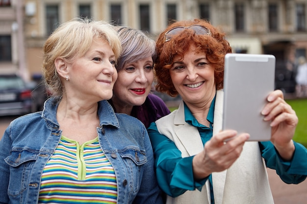 세 명의 웃는 중년 매력적인 여자 친구가 도시 거리에서 태블릿 pc로 셀카를 찍고 있습니다.