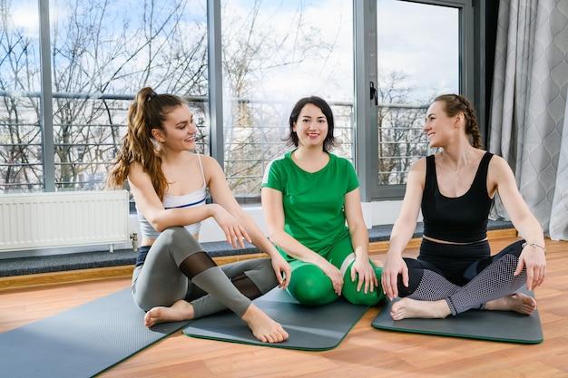 Три улыбающиеся спортивные женщины, сидящие босиком на циновках в легкой фитнес-студии