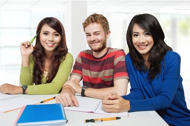 Три улыбающиеся студенты учатся вместе
