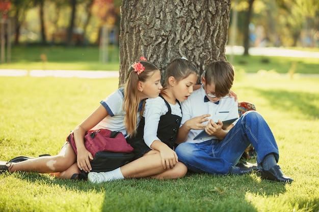 3 усмехаясь подростковых школьных друга сидя в парке на траве и играя новую игру таблетки совместно. разные эмоции на их лицах