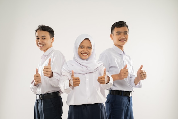 中学生の制服を着た3人の笑顔のティーンエイジャーが親指を立てて立っている