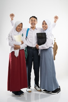 Three smiling teenagers wearing school uniforms with a backpack a book and a laptop computer