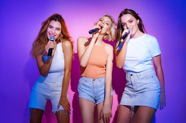 마이크에 노래를 부르는 웃는 세 소녀 밴드
