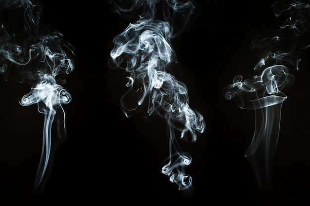 Three smoke silhouettes with abstract shapes