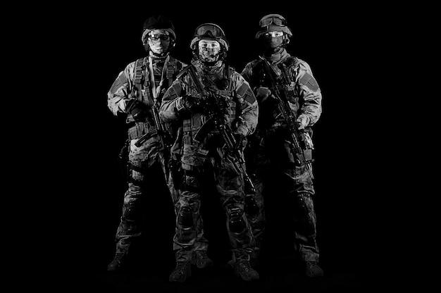 Грозно смотрят трое солдат в форме с оружием в руках. смешанная техника