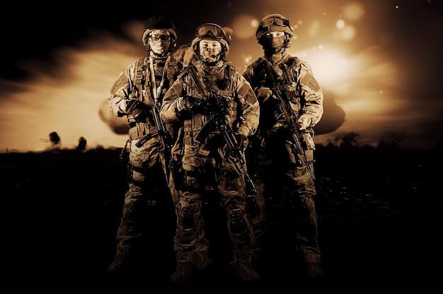손에 무기를 들고 제복을 입은 세 명의 군인이 위협적으로 보고 있습니다. 혼합 매체