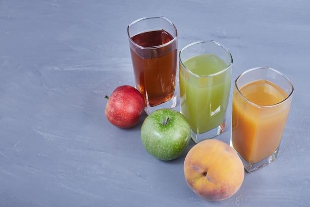 Tre tipi di frutta con bicchieri di succhi.