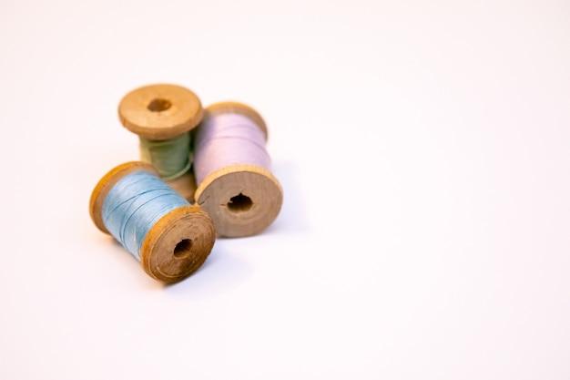 白い背景の上の糸の3つのスプール