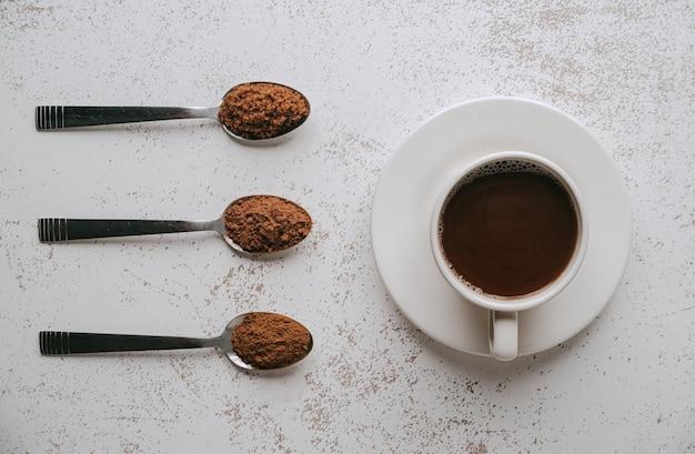 초콜렛을 준비하기위한 재료와 함께 세 숟가락. 그리고 작은 둥근 접시에 마실 준비가 된 초콜릿과 함께 컵.
