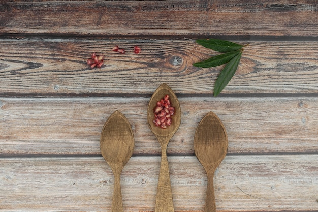 Three spoons of wood composition with pomegranate nuggets