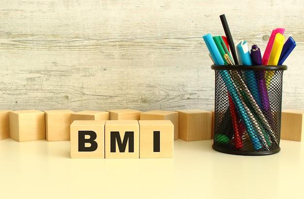 회색 배경에 흰색 바탕에 문자 bmi가 있는 3개의 쌓인 나무 큐브.