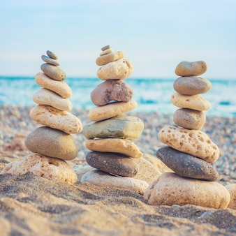 Three stacks of round smooth stones on the beach