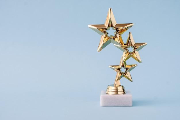 Три звезды за лидер и рейтинг. золотой блестящий приз на пастельно-синем фоне.