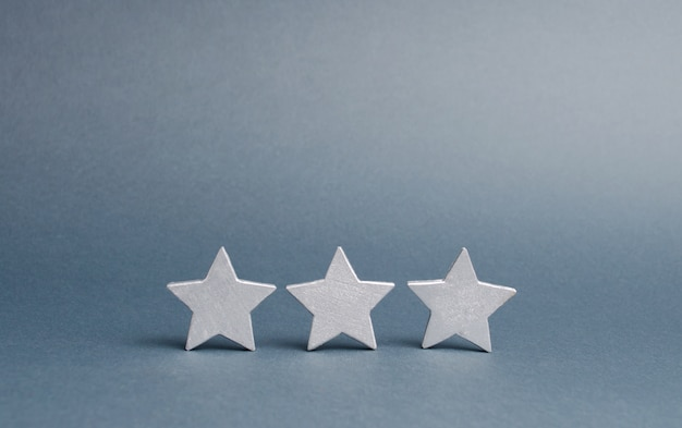 Three stars on a gray. the rating of the hotel, restaurant, mobile application