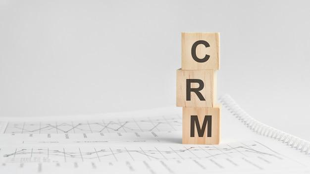 Три каменных куба на фоне белой финансовой отчетности, таблицы со словом crm - аббревиатура управления взаимоотношениями с клиентами. сильная бизнес-концепция. серый фон.