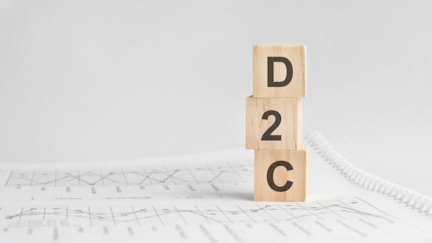 흰색 재무제표의 배경에 있는 세 개의 돌 큐브, d2c라는 단어가 있는 테이블. 강력한 비즈니스 개념