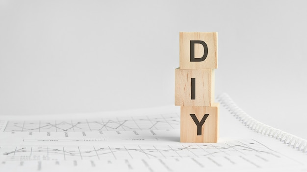 흰색 재무제표의 배경에 있는 세 개의 돌 큐브, diy라는 단어가 있는 테이블. 강력한 비즈니스 개념