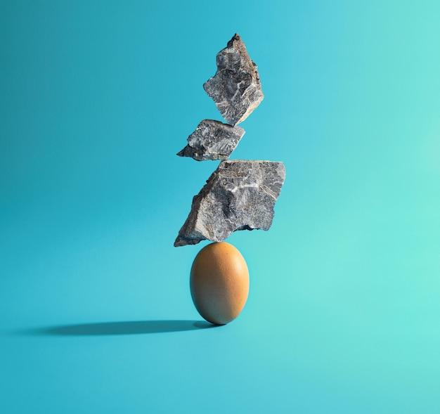 3個の石が卵にのっています。独創的なアイデア。バランスコンセプト