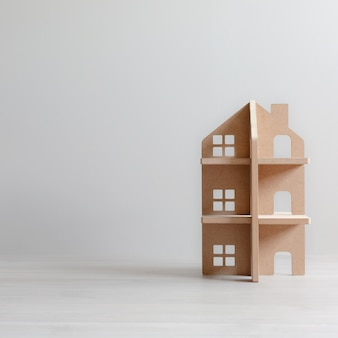 Three-storey wooden toy house in bright room with copy space.