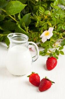 Three strawberries with milk