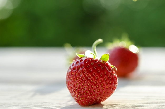 Three strawberries on a wooden table