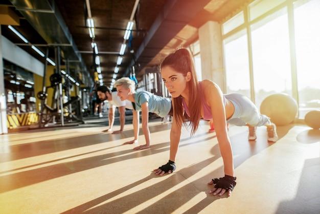 Трое сильных людей тренируются в тренажерном зале. отжимания в линию.